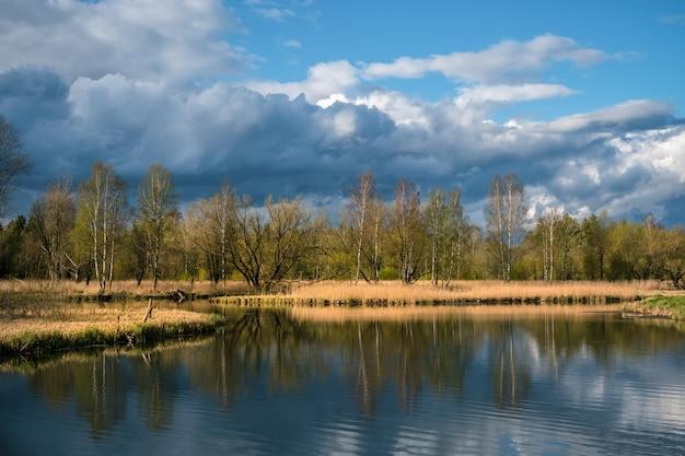 Paisagem de primavera russo com reflexos de árvores no lago