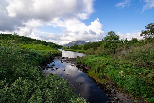 Paisagem de riacho de rio de montanha com montanhas cobertas de nuvens à distância.