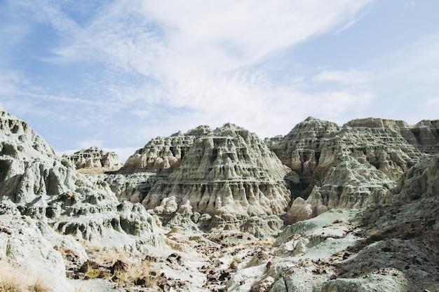 Paisagem de rochas cobertas de arbustos e musgos sob a luz do sol e um céu azul
