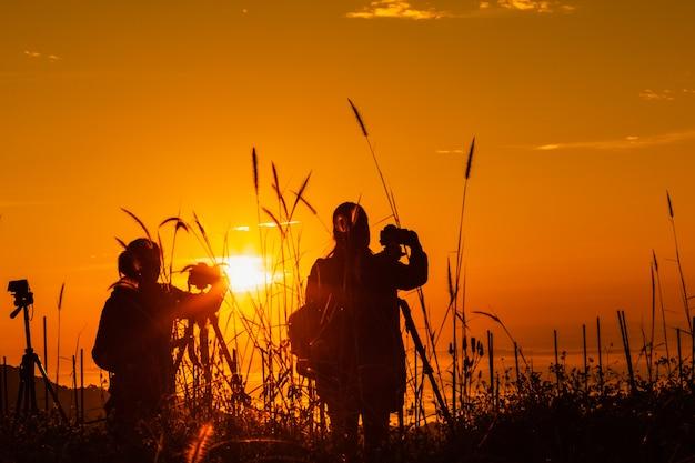 Paisagem de silhueta no turista de tempo de manhã tirar fotos do nascer do sol e névoa na montanha
