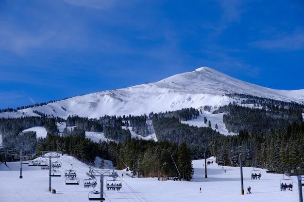 Paisagem de teleféricos cercados por colinas e florestas cobertas de neve sob um céu azul