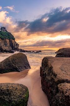Paisagem de tirar o fôlego de uma praia rochosa em um belo pôr do sol