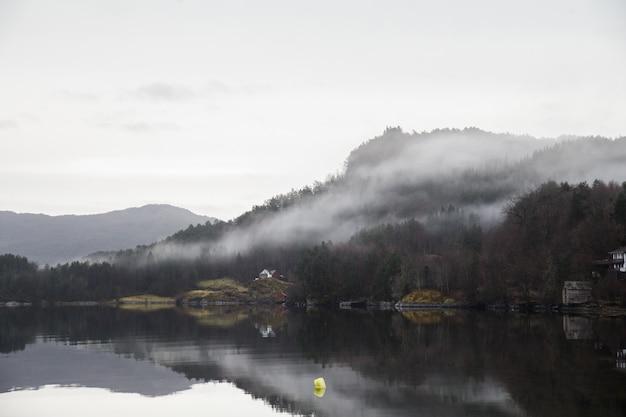 Paisagem de um lago cercado por montanhas cobertas de florestas e neblina, refletindo na água