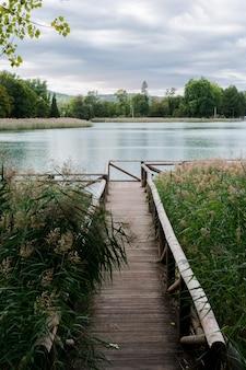 Paisagem de um lago onde aparece uma passarela