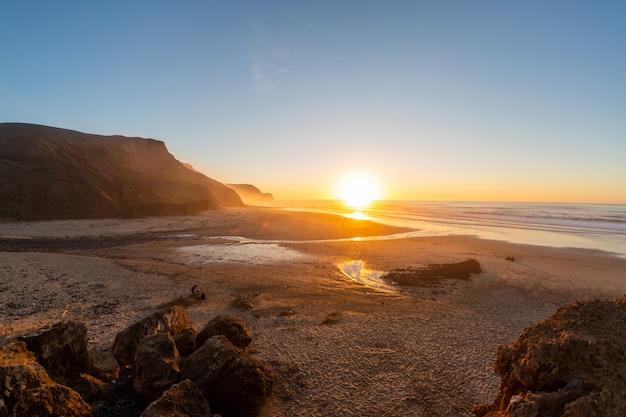 Paisagem de uma costa cercada por montanhas e mar sob um céu azul durante o pôr do sol