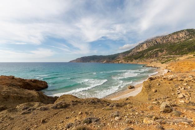 Paisagem de uma costa pedregosa cercada por vegetação sob um céu azul nublado em karpathos grécia