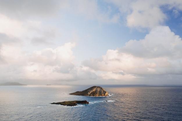 Paisagem de uma pequena ilha rodeada pelo mar sob um céu nublado e luz do sol