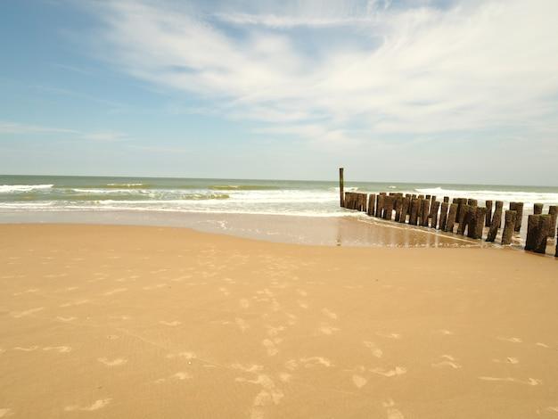 Paisagem de uma praia de areia com um quebra-mar de madeira nas laterais em um céu azul ensolarado e claro
