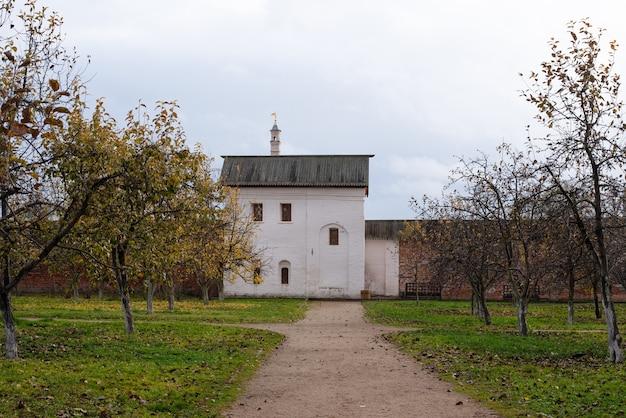 Paisagem de uma velha casa de tijolos brancos em um jardim de maçãs atrás de uma grande cerca de tijolos antigos. dia nublado de outono