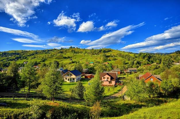 Paisagem de verão, casas rurais na encosta de montanhas verdes, contra o fundo de um céu azul com nuvens, árvores e abetos