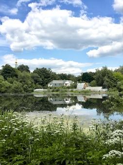 Paisagem de verão com casa de fazenda refletida na água do lago