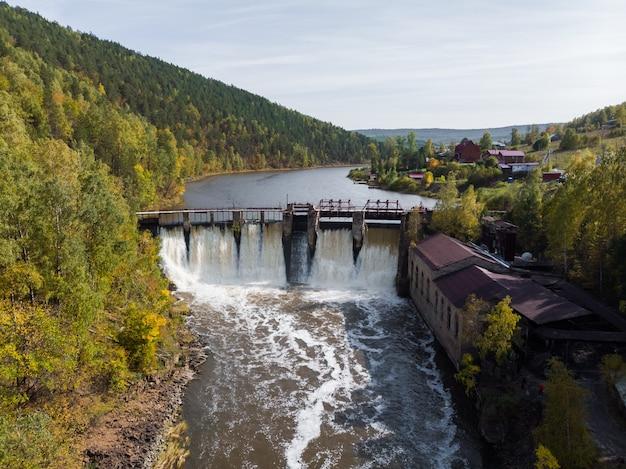 Paisagem de verão da velha barragem no rio em um fundo de montanhas e bosques em um dia ensolarado.
