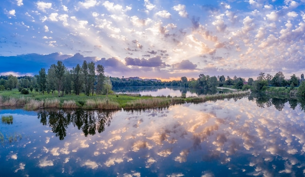 Paisagem de verão maravilhosa. nascer do sol sobre o lago. os raios do sol brilham através das nuvens.