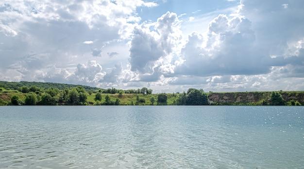 Paisagem de verão na zona rural com rio, floresta e nuvens.