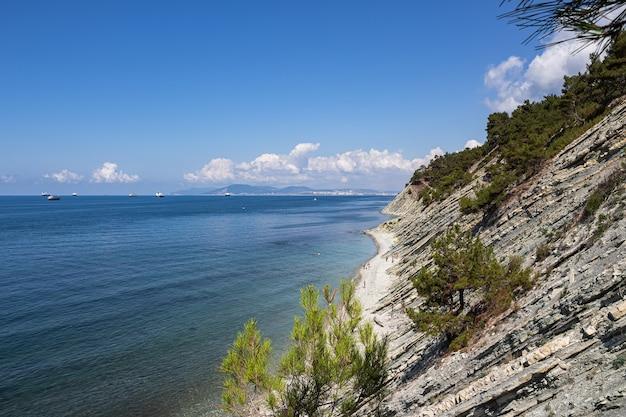 Paisagem de verão. uma pitoresca praia de pedra selvagem no sopé das rochas nas imediações do resort de gelendzhik e da cidade vizinha de novorossiysk. rússia, costa do mar negro
