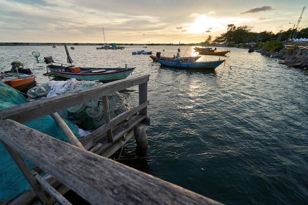 Paisagem de visão do porto de pesca latinos do sol há um pouso de barco.