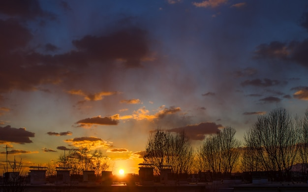 Paisagem deslumbrante do pôr do sol no céu nublado e silhuetas de árvores em zagreb, croácia