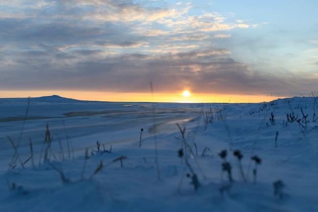 Paisagem do ártico no inverno. pequeno rio com gelo na tundra. pôr do sol.