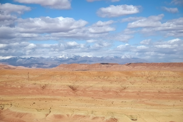 Paisagem do deserto com um céu azul nublado e montanhas cobertas de neve