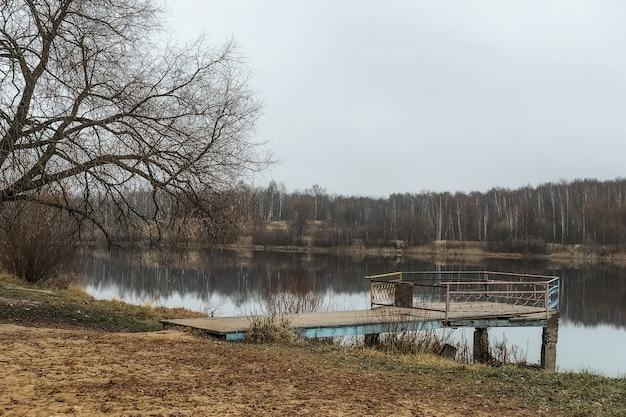 Paisagem do final do outono com o antigo cais abandonado na margem do lago e uma floresta sem folhas no horizonte