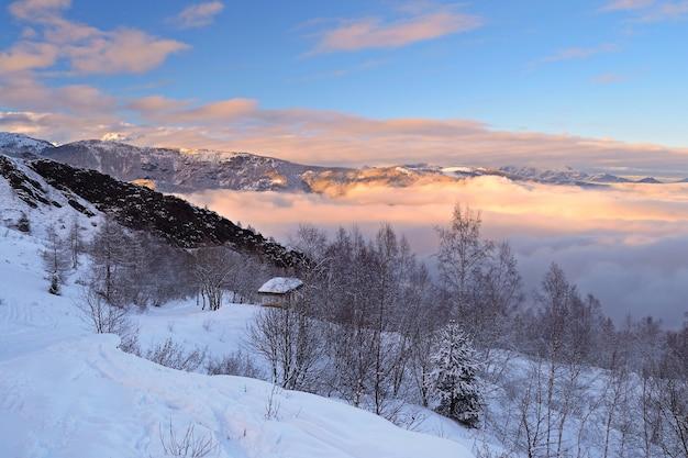 Paisagem do inverno ao pôr do sol, neve nos alpes