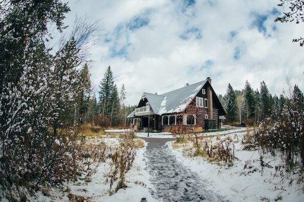 Paisagem do inverno com construção de casa na neve da floresta