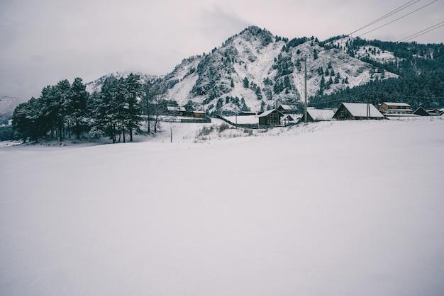 Paisagem do inverno com uma aldeia nas montanhas, na margem de um rio de montanha. dia gelado e nebuloso. morocromo.