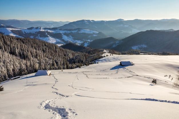 Paisagem do inverno do vale da montanha em um dia ensolarado gelado. caminho da pegada na neve branca profunda, levando a uma pequena cabana de pastor de madeira velha, colinas escuras arborizadas, sol brilhante no fundo do espaço da cópia do céu azul.