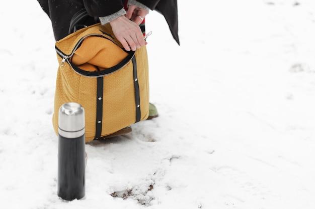 Paisagem do inverno e café em garrafa térmica