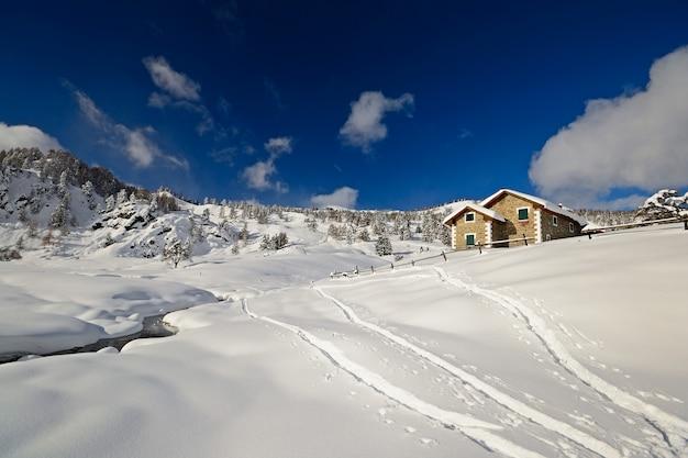 Paisagem do inverno nas montanhas italianas dos alpes e cabanas na neve