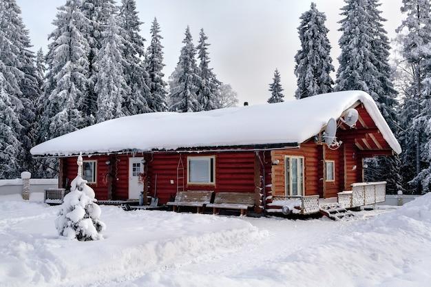Paisagem do inverno russo com troncos manchados de casa de campo marrom, com uma floresta de inverno e montes de neve.