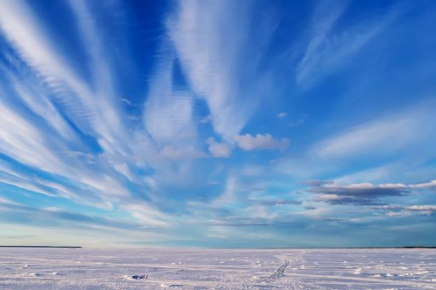 Paisagem do inverno sobre o rio congelado com céu azul brilhante e nuvens brancas