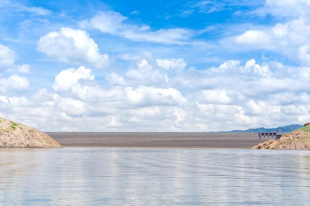Paisagem do lago e da represa concreta durante o dia ensolarado.