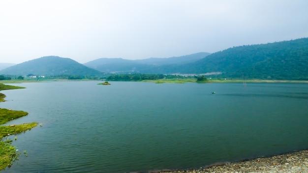 Paisagem do lago grande entre montanhas azuis