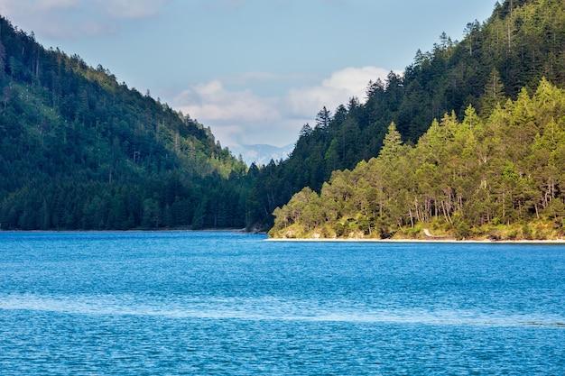 Paisagem do lago plansee com a costa coberta de madeira, na áustria.