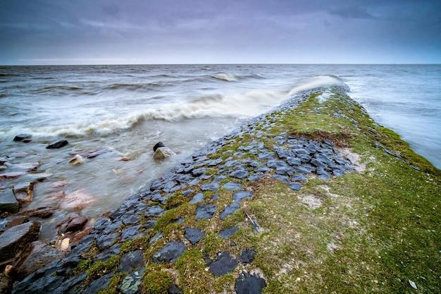 Paisagem do mar cercada por rochas cobertas de musgos sob um céu nublado ao anoitecer