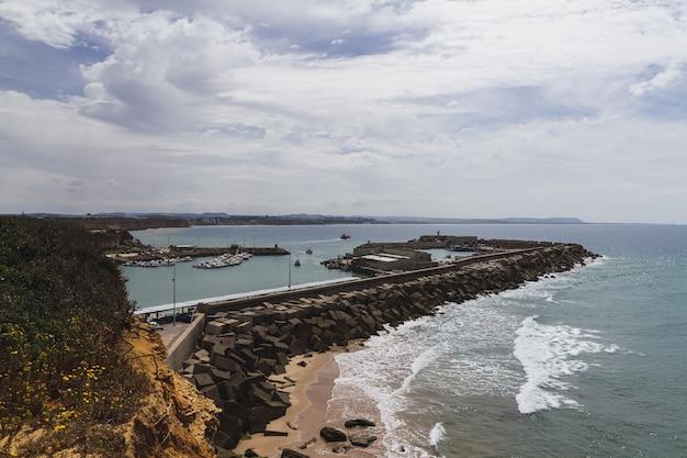 Paisagem do mar cercada por rochas sob um céu nublado e luz do sol durante o dia