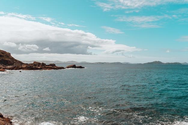 Paisagem do mar cercada por uma ilha coberta de verde sob um céu nublado