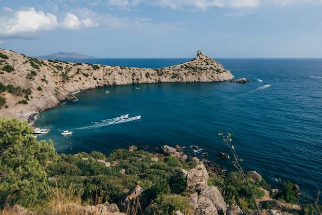 Paisagem do mar com baía azul e as montanhas de férias com os barcos