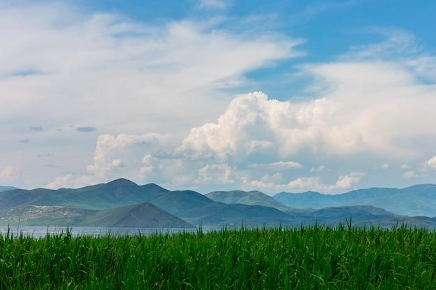 Paisagem do mar com mountines e bastões, céu azul com nuvens, sem o sol, cazaquistão