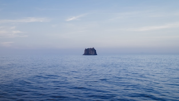 Paisagem do mar com uma rocha sob um céu nublado durante o dia