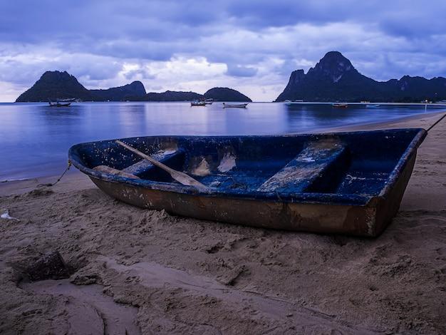 Paisagem do mar e pequeno barco na hora do crepúsculo, tailândia