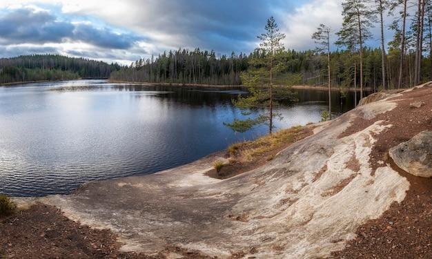 Paisagem do norte, lagos azuis entre a floresta de spruce. a natureza do istmo da carélia e as rochas do lago triangular.
