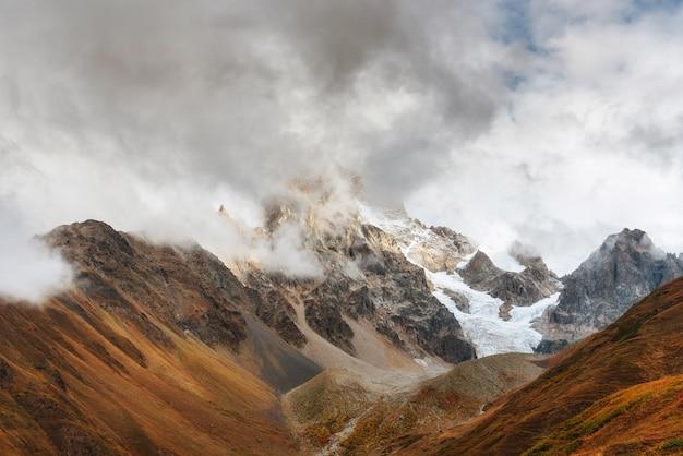 Paisagem do outono e montanhas da neve em nuvens de cumulus bonitas.