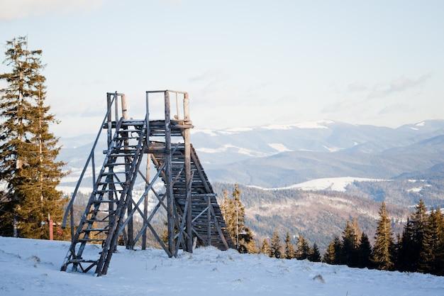 Paisagem do pôr do sol acima da floresta de inverno coníferas e salto de esqui