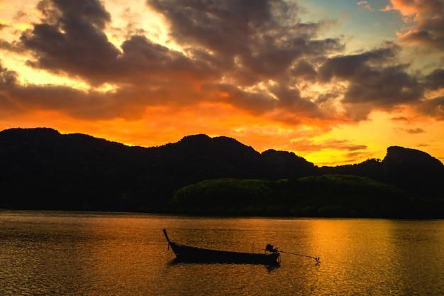 Paisagem do pôr do sol, céu na hora do crepúsculo com pequenos barcos de pesca na tailândia
