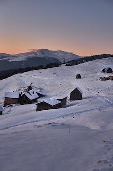 Paisagem do pôr do sol de inverno com casas de madeira em montanhas nevadas