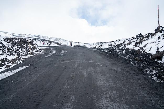 Paisagem do terreno selvagem do vulcão etna com estradas de neve e cinzas no topo do vulcão