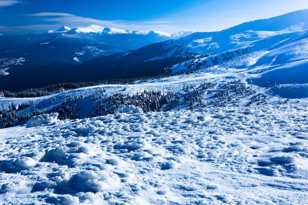 Paisagem do vale de inverno neve, montanhas e sol acima em dia gelado de inverno claro.
