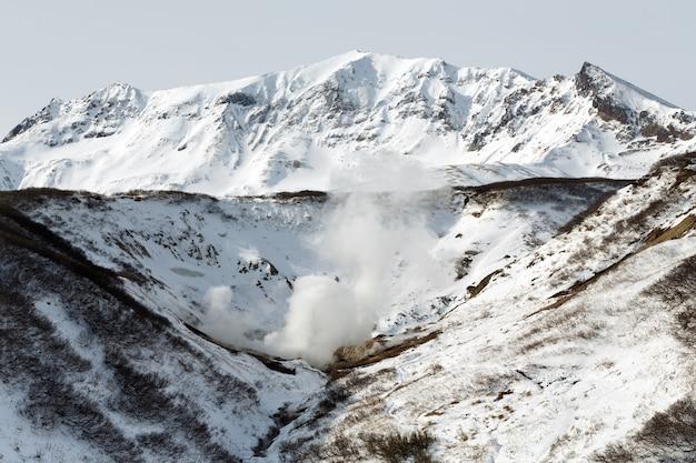 Paisagem do vulcão ativo vista de inverno da atração das fontes termais do vale geotérmico na zona vulcânica